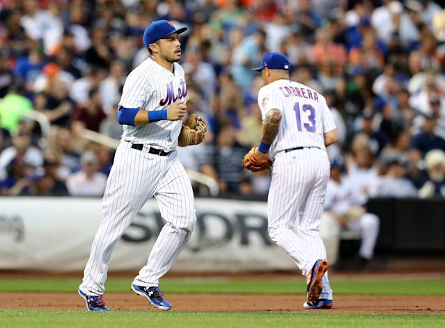 Travis d'Arnaud (left) and Asdrubal Cabrera (right) make one of their 22 position swaps during Wednesday's game against the Yankees. (Getty Images)