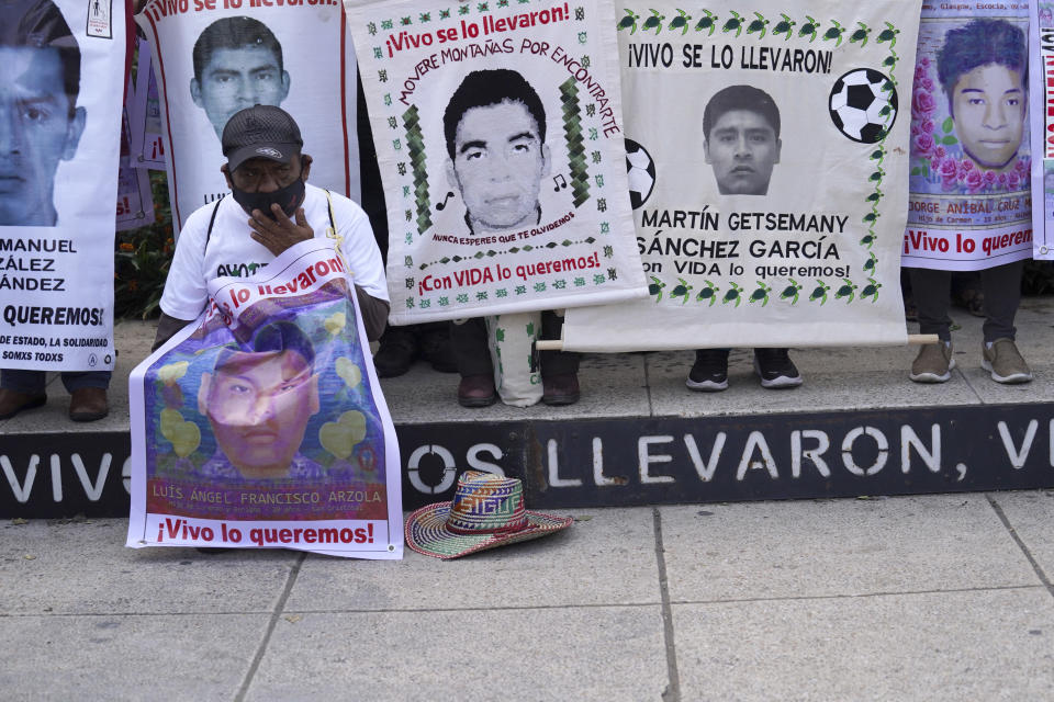 A relative of one of the 43 missing university students holds a placard with s photo of his loved one, as he joins others in a march on the seventh anniversary of their disappearance, in Mexico City, Sunday, Sept. 26, 2021. Relatives continue to demand justice for the Ayotzinapa students who were allegedly taken from the buses by the local police and handed over to a gang of drug traffickers. (AP Photo/Marco Ugarte)