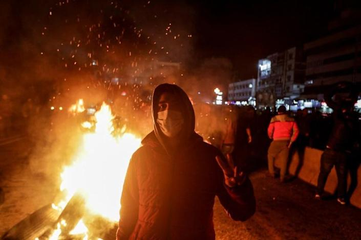 Protesters burned tyres to block a highway north of Beirut on Tuesday to protest against the newly named government (AFP Photo/JOSEPH EID)