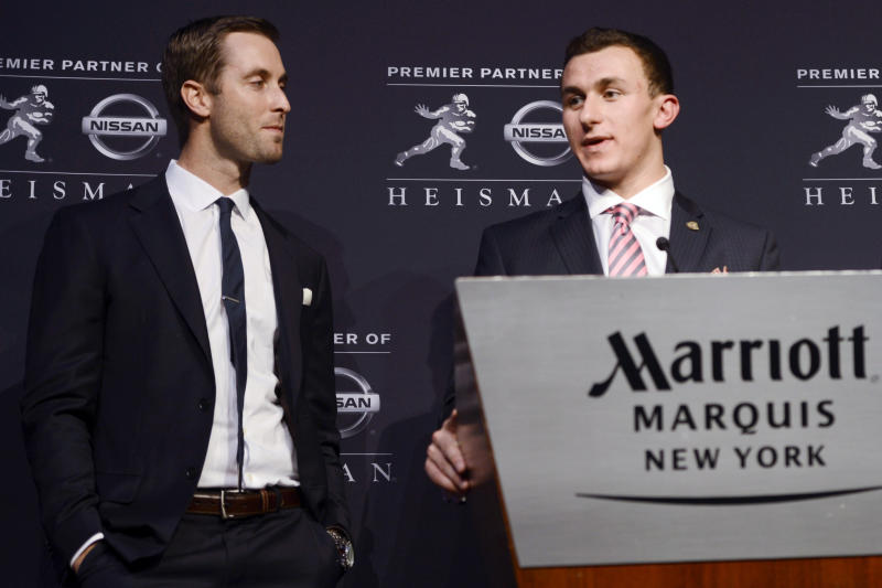 FILE - In this Dec. 8, 2012, file photo, Texas A&M offensive coordinator Kliff Kingsbury, left, watches as quarterback Johnny Manziel speaks after becoming the first freshman to win NCAA college football's Heisman Trophy in New York. Kingsbury was hired Wednesday, Dec. 12, as the new head coach of Texas Tech, where he was the first in a string of record-setting quarterbacks under former coach Mike Leach. (AP Photo/Henny Ray Abrams, File)