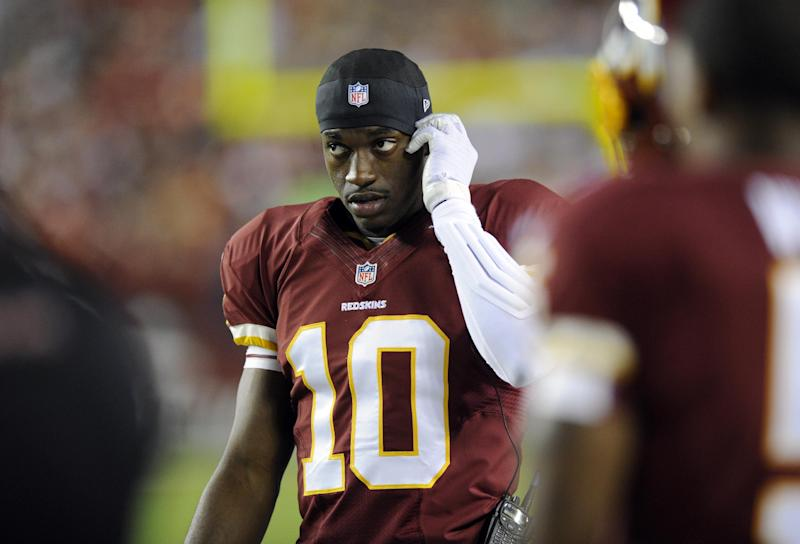 Washington Redskins quarterback Robert Griffin III (10) listens to the play calls on a radio while on the sidelines during the first half of an NFL preseason football game against the Pittsburgh Steelers, Monday, Aug. 19, 2013, in Landover, Md. (AP Photo/Nick Wass)
