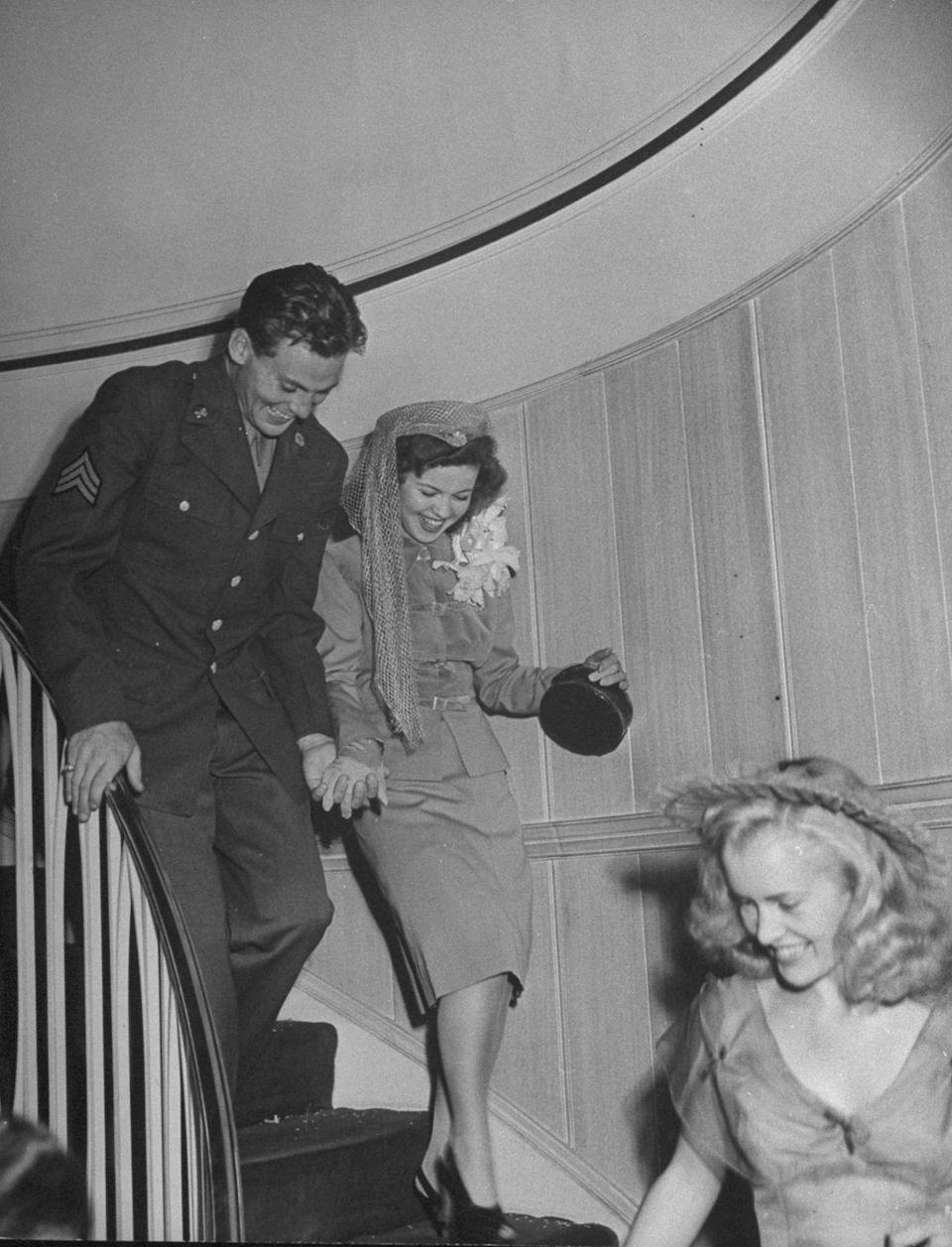 <p>After hosting a large reception in her Hollywood home, Shirley Temple traded her long-sleeve satin wedding gown for a grey belted suit, as she and her new husband, Army Sargent John Agar, departed for their honeymoon. The couple was all smiles as their friends and family sent them off as newlyweds. <br></p>
