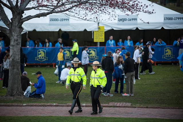 BOSTON, MA - APRIL 21: Police officers monitor runners getting ready to run the Boston Marathon in the Boston Commons on April 21, 2014 in Boston, Massachusetts. Today marks the 118th Boston Marathon; security presence has been increased this year, due to two bombs that were detonated at the finish line last year, killing three people and injuring more than 260 others. (Photo by Andrew Burton/Getty Images)