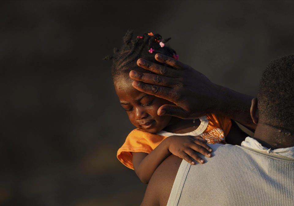 A man carries a girl across the Rio Grande river as migrants, many from Haiti, leave Del Rio, Texas to return to Ciudad Acuna, Mexico, early Wednesday, Sept. 22, 2021, some to avoid possible deportation from the U.S. and others to get supplies. (AP Photo/Fernando Llano)