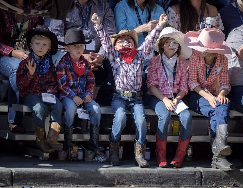 <p>Young children wearing hats and bandanas appear excited to attend the Calgary Stampede parade in Calgary on July 6, 2018. Photo from The Canadian Press. </p>