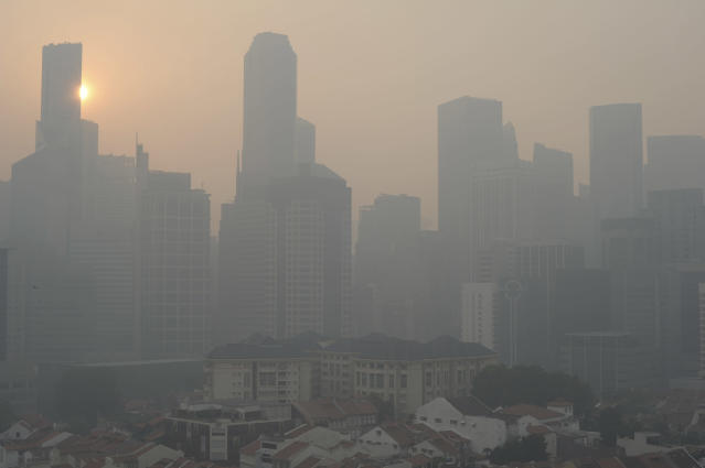 The sun rises over the Singapore Central Business District, or CBD skyline as the haze or smog envelopes the city on Thursday, June 20, 2013. A smoky haze triggered by forest fires in neighboring Indonesia has caused air pollution to briefly hit its worst level in nearly 16 years in Singapore. (AP Photo/Joseph Nair)
