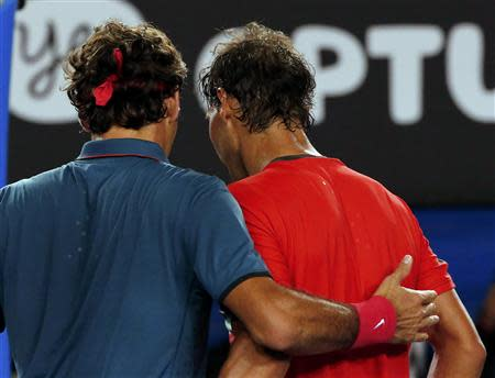 Rafael Nadal (R) of Spain and Roger Federer of Switzerland hug at the net, after Nadal won their men's singles semi-final match at the Australian Open 2014 tennis tournament in Melbourne January 24, 2014. REUTERS/Petar Kujundzic
