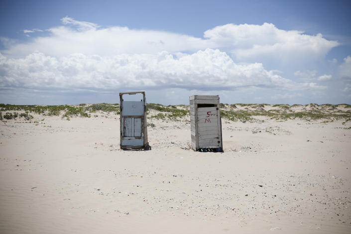 In this Aug. 3, 2019 photo, two public restrooms dot the landscape on Playa Bagdad near the border city of Matamoros, Mexico. The last thing the drug cartels want, is to draw U.S. patrols to the area, which is already hard to reach by any normal route. It is precisely that remoteness and lack of patrols that serves the drug trade, the economic activity that has become the mainstay here. (AP Photo/Emilio Espejel)