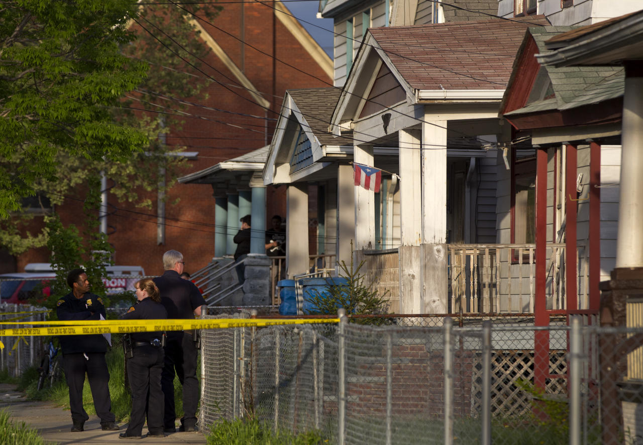Cleveland Police stand outside a home where they say missing women, Amanda Berry, Gina DeJesus and Michele Knight were found in the 2200 block of Seymour Avenue in Cleveland on Monday, May 6, 2013. The three women who went missing about a decade ago were found alive in a residential area just south of downtown, and a man was arrested. (AP Photo/Plain Dealer, Scott Shaw)