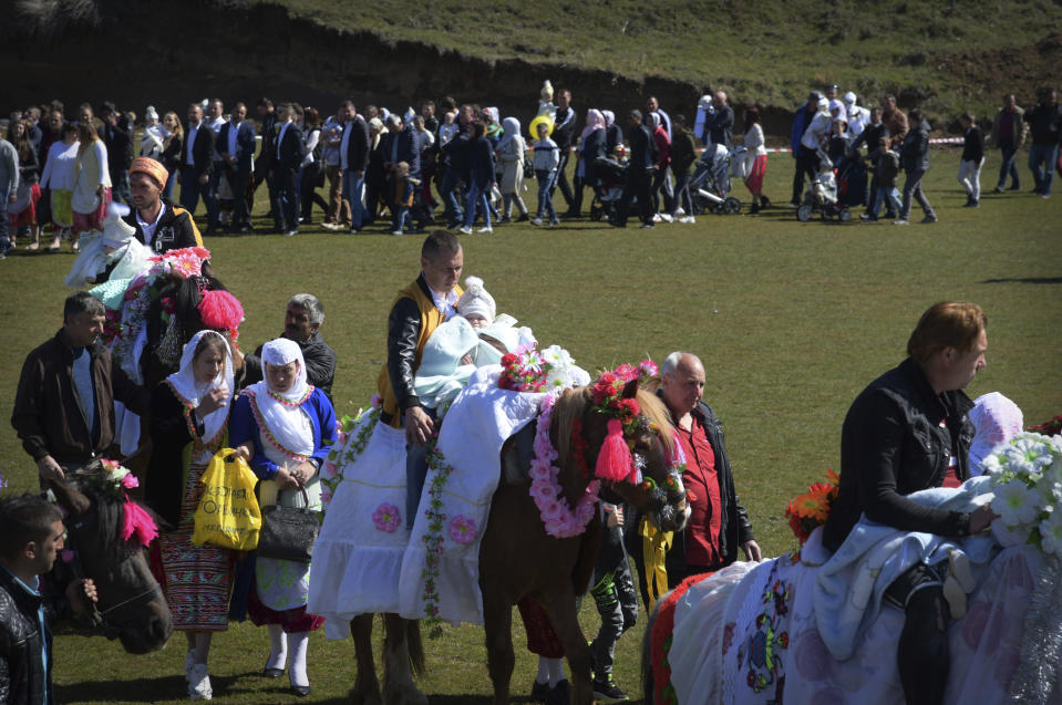 Bulgarian muslims walk in a procession during mass circumcision ceremony in the village of Ribnovo, Bulgaria, Sunday, April 11, 2021. Despite the dangers associated with COVID-19 and government calls to avoid large gatherings, Hundreds of people flocked to the tiny village of Ribnovo in southwestern Bulgaria for a four-day festival of feasting, music and the ritual of circumcision which is considered by Muslims a religious duty and essential part of a man's identity. (AP Photo/Jordan Simeonov)