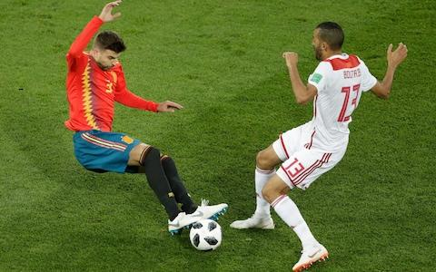 Spain's Gerard Pique, left, and Morocco's Khalid Boutaib, right, compete for the ball during the group B match between Spain and Morocco at the 2018 soccer World Cup in the Kaliningrad Stadium in Kaliningrad - Credit: AP Photo/Michael Sohn