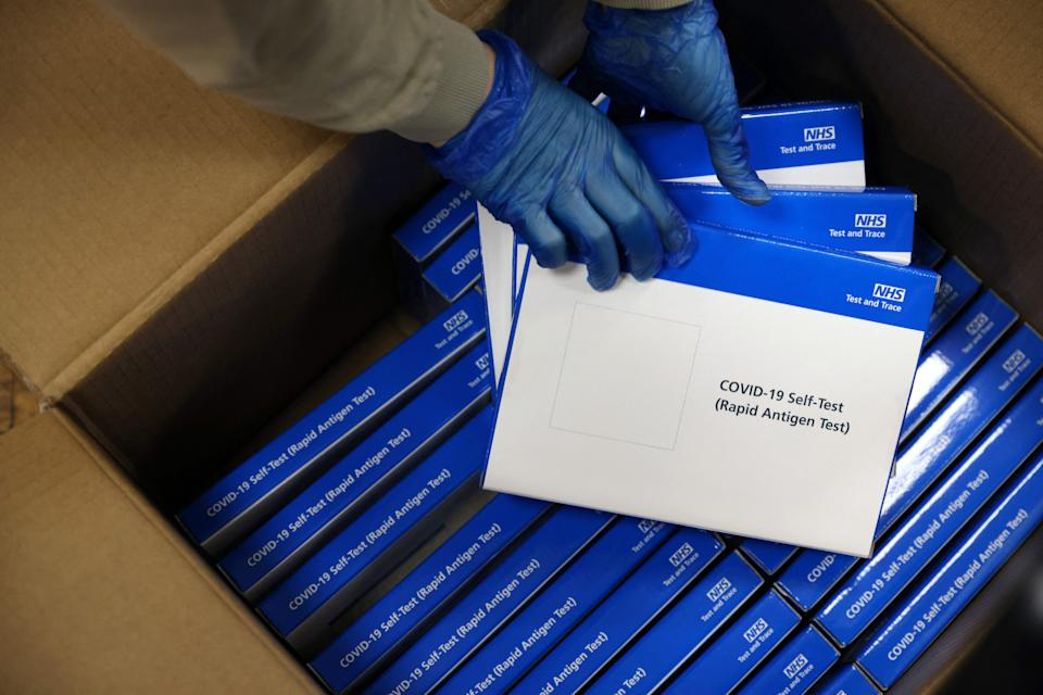 A health worker removes Covid-19 test kits from a box at a NHS Test and Trace Covid-19 testing unit at the Civic Centre in Uxbridge, Hillingdon, west London on May 25, 2021, as