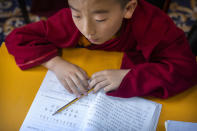 """A young monk dubbed as a recognized reincarnation or """"living Buddha"""" studies a Chinese-language textbook during a class at the Tibetan Buddhist College near Lhasa in western China's Tibet Autonomous Region, Monday, May 31, 2021, as seen during a government organized visit for foreign journalists. High-pressure tactics employed by China's ruling Communist Party appear to be finding success in separating Tibetans from their traditional Buddhist culture and the influence of the Dalai Lama. (AP Photo/Mark Schiefelbein)"""