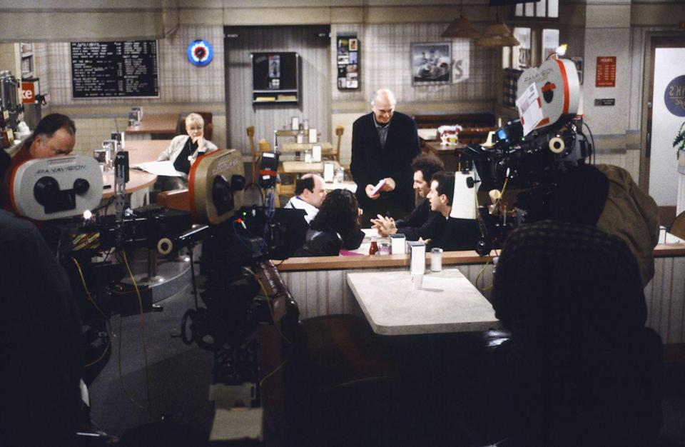 <p>The diner was the gang's meeting place over the course of the show. Here, David is seen giving the cast a few notes between takes.</p>