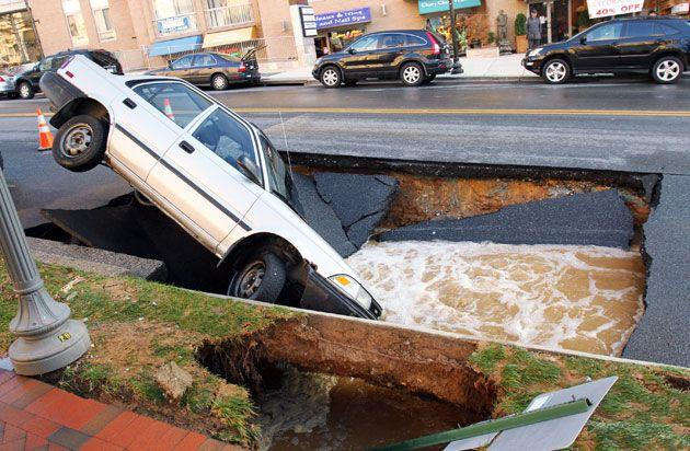 A car sits in a sinkhole caused by a broken water main, which collapsed part of Friendship Blvd back in Maryland in 2010. Credit: Getty