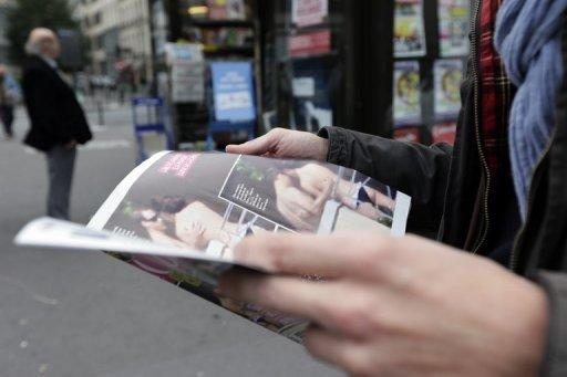 A man holds a copy of the celebrity magazine Closer, which published topless pictures of Prince William's wife Catherine, Duchess of Cambridge, taken while the pair were on holiday in France