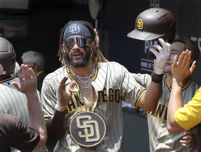 San Diego Padres' Fernando Tatis Jr. gets high fives in the dugout after hitting a two run home run during the fifth inning in the first game of a baseball doubleheader against ther Atlanta Braves Wednesday, July 21, 2021, in Atlanta. The Padres won 3-2. (Curtis Compton/Atlanta Journal-Constitution via AP)