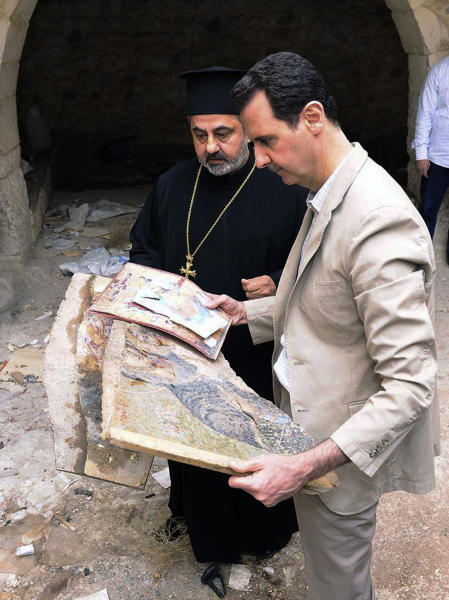 """In this photo released by the Syrian official news agency SANA, Syrian President Bashar Assad, right, holds a broken religious mosaic during his visit to the Christian village of Maaloula, near Damascus, Syria, Sunday April, 20, 2014. Assad toured a historic Christian village his forces recently captured from rebels, state media said, as the country's Greek Orthodox Patriarch vowed that Christians in the war-ravaged country """"will not submit and yield"""" to extremists. The rebels, including fighters from the al-Qaida-affiliated Nusra Front, took Maaloula several times late last year. (AP Photo/SANA)"""