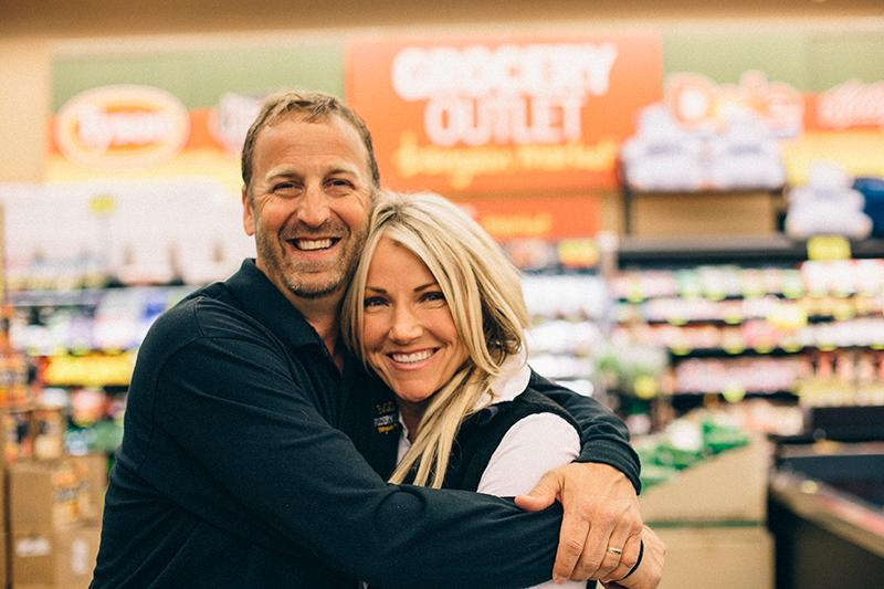 A man and a woman hugging inside a Grocery Outlet store.