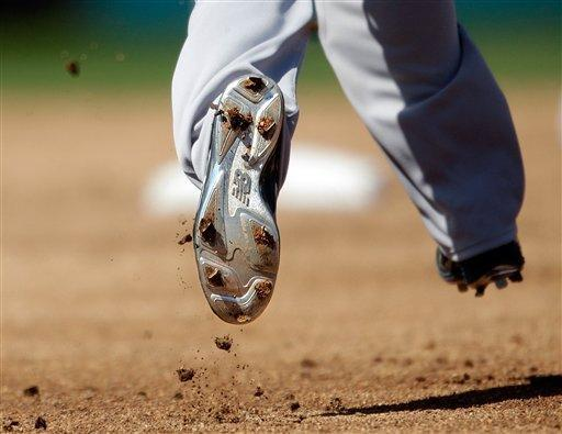 Dirt falls off the cleat of Boston Red Sox's Dustin Pedroia as he runs to second base on a single by teammate Mike Napoli in the third inning of a spring training exhibition baseball game against the Minnesota Twins, Thursday, March 7, 2013, in Fort Myers, Fla. (AP Photo/David Goldman)