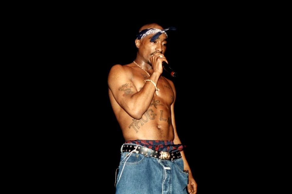 Tupac performs on stage shirtless wearing signature bandana. Source: Getty Images
