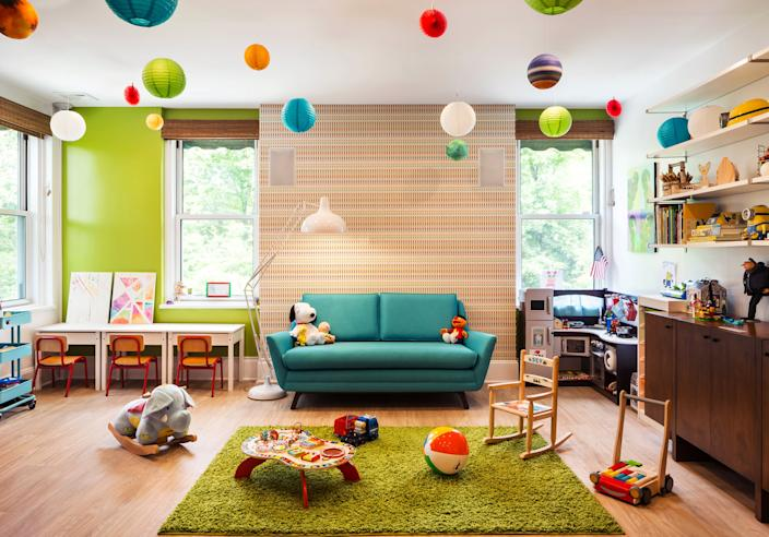 "<div class=""caption""> The playroom is a riot of color. ""I try to sneak some wallpaper into every project, if I can,"" says McLeod. Here, she chose a multicolored print from <a href=""https://www.stylelibrary.com/"" rel=""nofollow noopener"" target=""_blank"" data-ylk=""slk:Style Library"" class=""link rapid-noclick-resp"">Style Library</a> and paired it with an accent wall painted <a href=""https://www.benjaminmoore.com/en-us"" rel=""nofollow noopener"" target=""_blank"" data-ylk=""slk:Benjamin Moore"" class=""link rapid-noclick-resp"">Benjamin Moore</a>'s Tequila Lime. The loveseat is from <a href=""https://joybird.com/"" rel=""nofollow noopener"" target=""_blank"" data-ylk=""slk:Joybird"" class=""link rapid-noclick-resp"">Joybird</a>, the rug from <a href=""https://www.wayfair.com/"" rel=""nofollow noopener"" target=""_blank"" data-ylk=""slk:Wayfair"" class=""link rapid-noclick-resp"">Wayfair</a>, and the children's desks and shelves are from <a href=""https://www.ikea.com/us/en/"" rel=""nofollow noopener"" target=""_blank"" data-ylk=""slk:IKEA"" class=""link rapid-noclick-resp"">IKEA</a>. The sideboard was repurposed from the client's previous home. </div>"