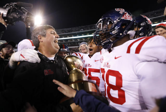 Mississippi coach Matt Luke, left, celebrates with players following their 31-28 win over Mississippi State in the Egg Bowl NCAA college football game in Starkville, Miss., Thursday, Nov. 23, 2017. (AP Photo/Rogelio V. Solis)