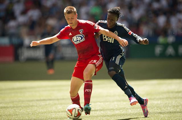 FC Dallas' Walker Zimmerman, left, forces Vancouver Whitecaps' Darren Mattocks, of Jamaica, off the ball during the first half of an MLS soccer game in Vancouver, British Columbia, on Sunday July 27, 2014. (AP Photo/The Canadian Press, Darryl Dyck)