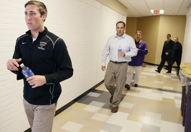 Minnesota State, Mankato football player Sam Thompson left, associate head coach Aaron Keen and coach Todd Hoffner coach arrive for a news conference Thursday, April 17, 2014, in Mankato, Minn. Players ended their boycott of spring practice and said Thursday they will play for Hoffner, who was reinstated after being exonerated of having child pornography on his cellphone. (AP Photo/Star Tribune, Jerry Holt)