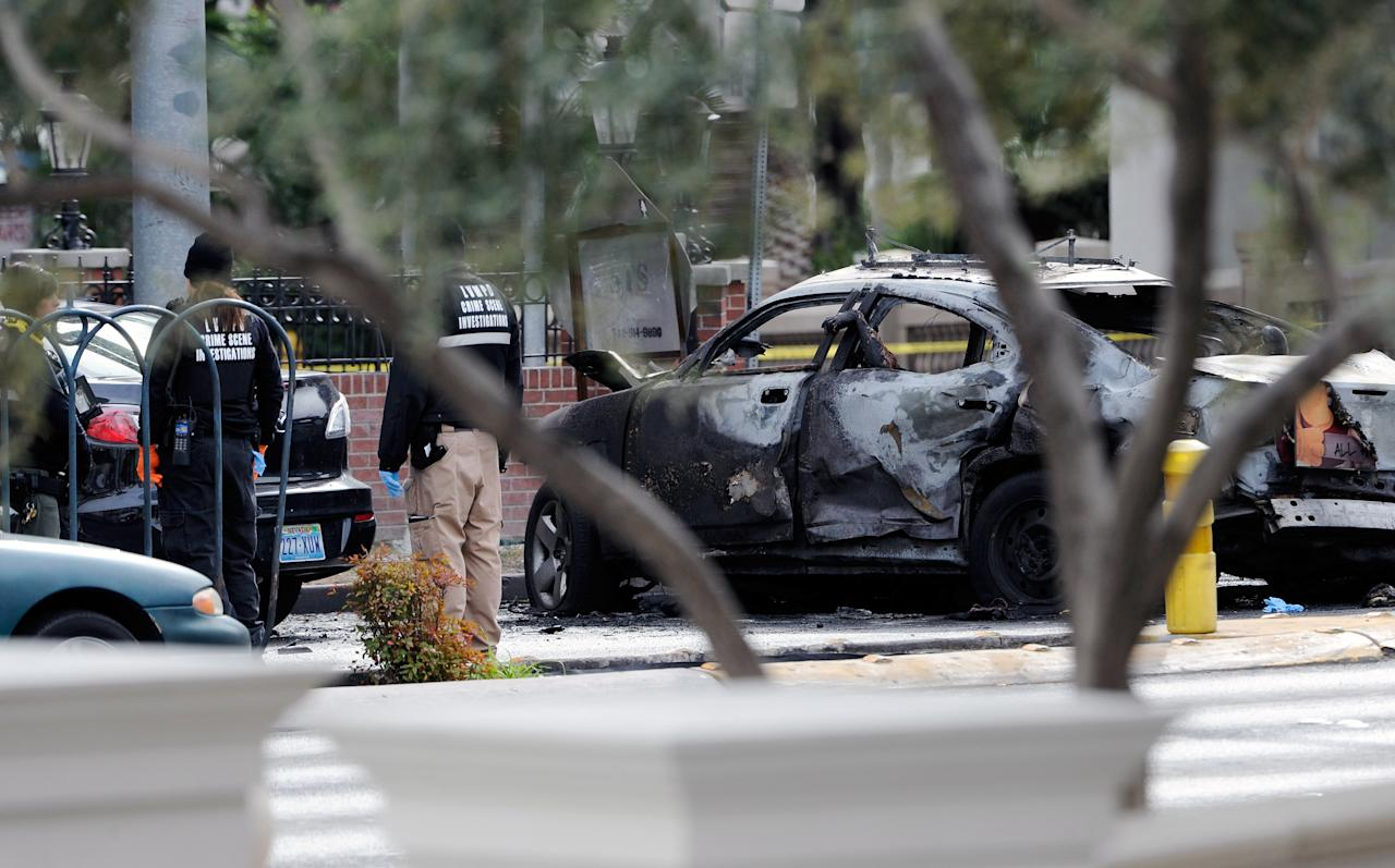 LAS VEGAS, NV - FEBRUARY 21:  (EDITORS NOTE: Image contains graphic content.)  A burned taxi cab sits at the site of what is being described as a gun battle between shooters in two vehicles along the Las Vegas Strip on February 21, 2013 in Las Vegas, Nevada. According to reports gunshots were fired between a black SUV and a Maserati, causing the Maserati to crash into a taxi that burst into flames. Five vehicles were involved in the subsequent crash with the Maserati driver and two people in the taxi being killed.  (Photo by David Becker/Getty Images)