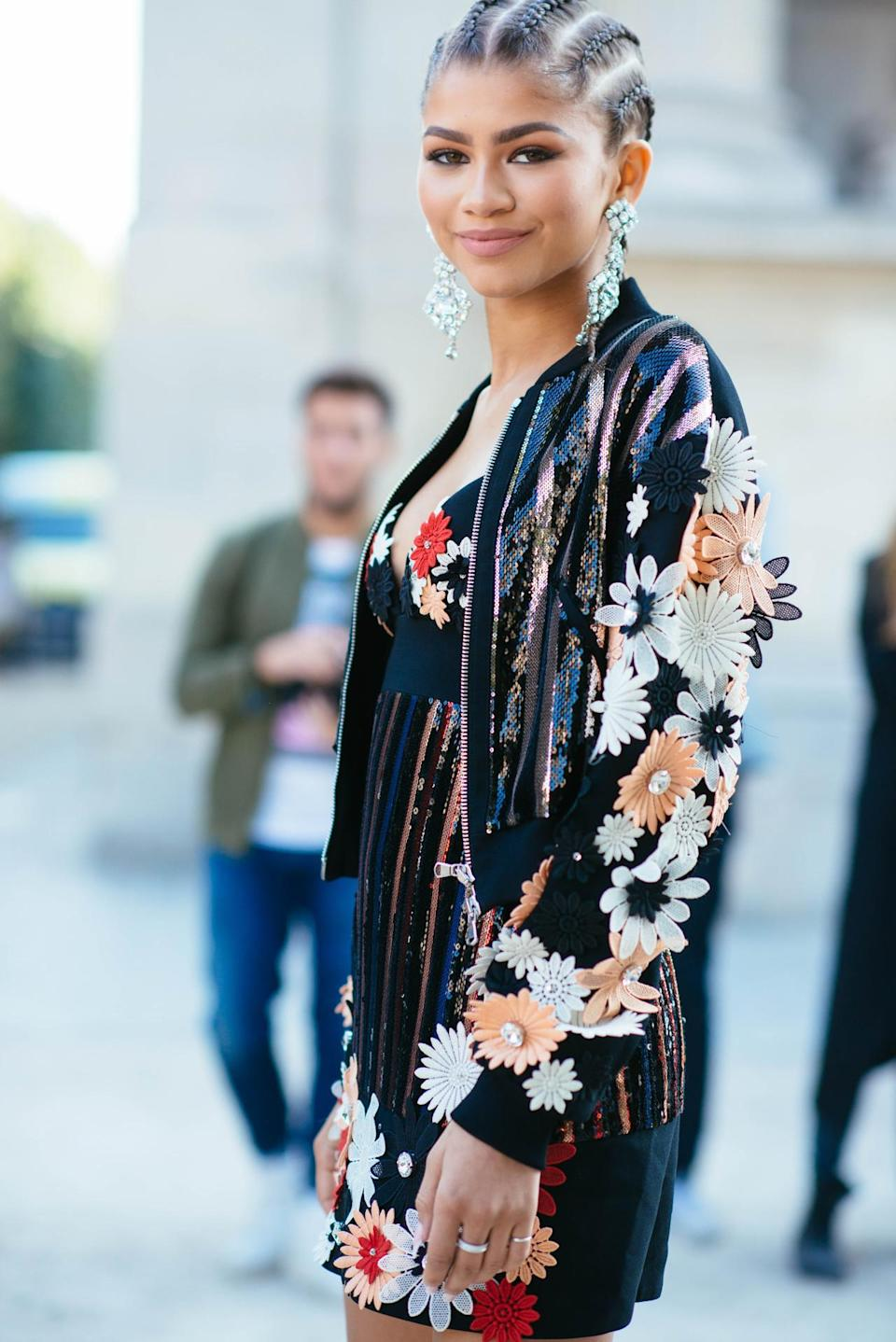 "<p>Attending Emanuel Ungaro's Spring 2016 fashion show, Zendaya paired a black dress covered in sequins and red, peach, pink, and white flowers blooming off it. She paired the mini with a matching bomber jacket made of the same elements. When she shared a pic of herself in this outfit, she captioned it cornrows and designer clothes. On her changing hairstyles, the <i>K.C. Undercover</i> star <a href=""https://instagram.com/p/8aeV2rpmBT/?taken-by=zendaya"" rel=""nofollow noopener"" target=""_blank"" data-ylk=""slk:wrote on Twitter"" class=""link rapid-noclick-resp"">wrote on Twitter</a>, ""A guy came up to me and was like, 'One show you have short hair, now you have braids, how?' I turned over my shoulder and said…magic."" </p><p><i>Photo: BFA</i></p>"