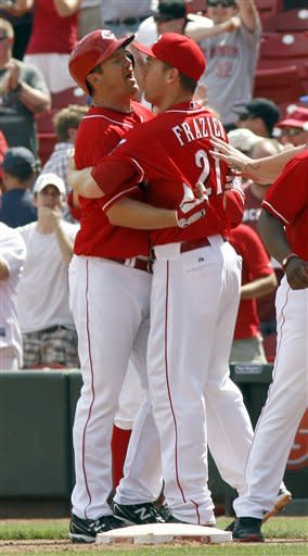 Cincinnati Reds' Scott Rolen, left, is congratulated by Todd Frazier, right, after Rolen hit a game-winning sacrifice fly off Chicago Cubs relief pitcher Rafael Dolis during the 10th inning of a baseball game, Thursday, May 3, 2012, in Cincinnati. The Reds won 4-3. (AP Photo/David Kohl)
