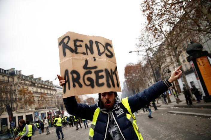 """A protester wearing a yellow vest holds a placard reading """"Give back money"""" on the Champs-Elysees Avenue during a national day of protest by the """"yellow vests"""" movement in Paris, France, Dec. 8, 2018. (Photo: Christian Hartmann/Reuters)"""