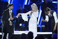 <p>This glorious gown highlights Dolly at her best in a sparkling, all-white ensemble worn at the 53rd Annual CMA Awards in 2019. As much as sparkles have become a hallmark of the singer's style, her big heart has become a hallmark of her legacy that is sure to endure for generations. </p>
