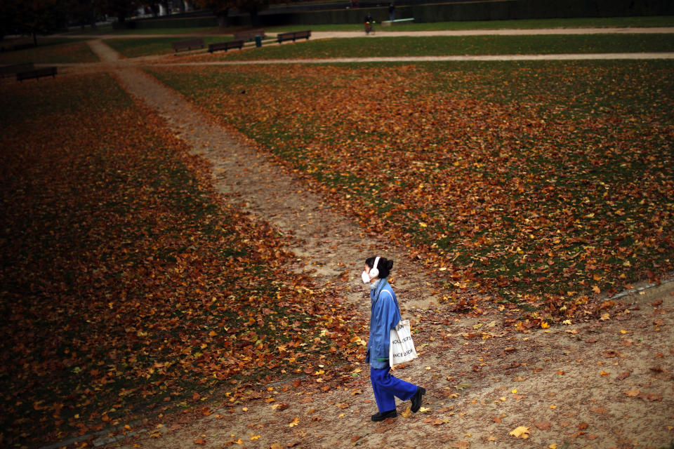 A woman, wearing a face mask to prevent the spread of the coronavirus COVID-19, walks along Cinquantenaire park in an autumn day in Brussels, Friday, Oct. 23, 2020. Belgian Prime Minister Alexander De Croo stopped short Friday of imposing another full lockdown, as the country did in March, but introduced a series of new restrictive measures as the number of COVID-19 related hospital admissions and deaths continue to soar. (AP Photo/Francisco Seco)