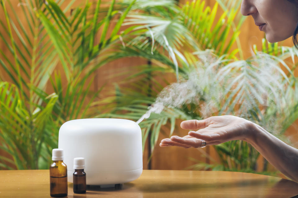 A woman enjoying aromatherapy steam scent from home essential oil diffuser. (PHOTO: Getty Images)