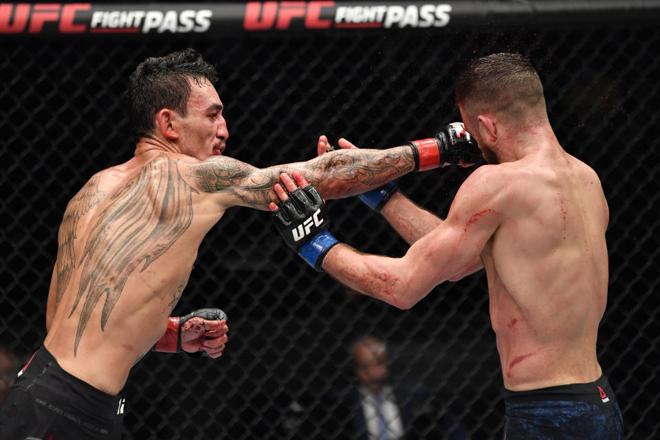 ABU DHABI, UNITED ARAB EMIRATES - JANUARY 17: (L-R) Max Holloway punches Calvin Kattar in a featherweight bout during the UFC Fight Night event at Etihad Arena on UFC Fight Island on January 17, 2021 in Abu Dhabi, United Arab Emirates. (Photo by Jeff Bottari/Zuffa LLC)