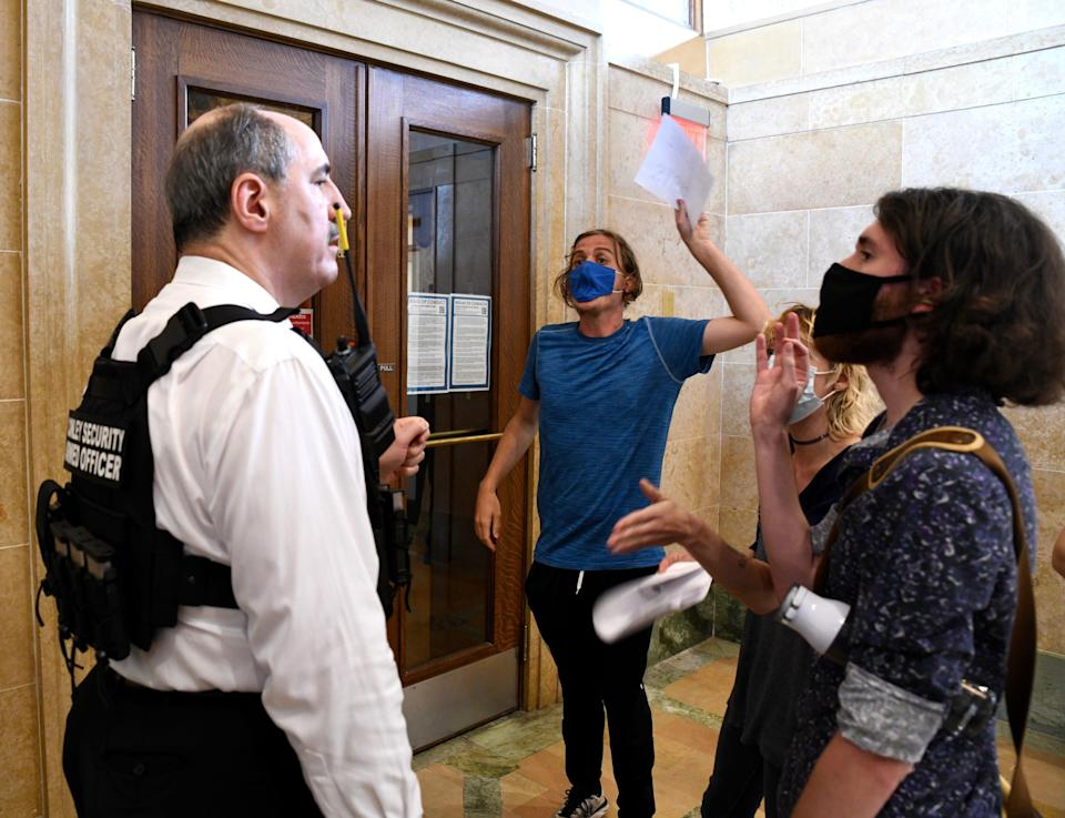 Tom Conley, president and CEO of private security firm Conley Group, argues with John Noble, 26, as Noble demands to know why he and others were being denied access to a Des Moines City Council meeting on June 28.