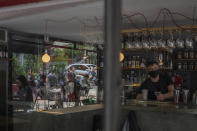 A bartender wearing a protective face mask prepares a drink as people sitting outdoor are reflected on a window of Lola cafe-bar in Petralona, district of Athens, Monday, May 3, 2021. Pandemic-weary travelers are returning to the skies and casinos in the United States and eating out again in Greece as the vaccine rollout is sending news cases and deaths tumbling in more affluent countries, contrasting with a worsening disaster in India. (AP Photo/Petros Giannakouris)