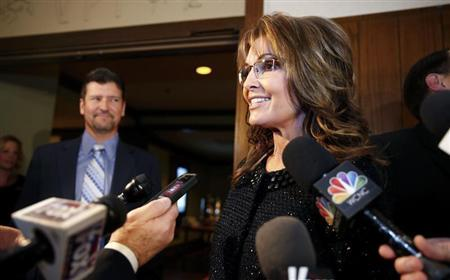 Former Republican governor of Alaska Sarah Palin speaks to members of the media as her husband Todd looks on before a celebration for evangelist Billy Graham's 95th birthday in Asheville, North Carolina November 7, 2013. REUTERS/Chris Keane