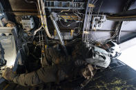 """U.S. Marine Cpl. Thalles Souza, rests as a VM-22 Osprey, flies back to base after departing Jeremie Airport, Saturday, Aug. 28, 2021, in Jeremie, Haiti. The VMM-266, """"Fighting Griffins,"""" from Marine Corps Air Station New River, from Jacksonville, N.C., are flying in support of Joint Task Force Haiti after a 7.2 magnitude earthquake on Aug. 22, caused heavy damage to the country. (AP Photo/Alex Brandon)"""