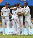 India's Mohammed Siraj, centre, celebrates with teammate Mayank Agarwal, second left, after taking his fifth wicket during play on day four of the fourth cricket test between India and Australia at the Gabba, Brisbane, Australia, Monday, Jan. 18, 2021. (AP Photo/Tertius Pickard)