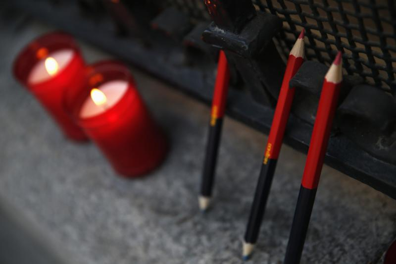 Pencils and candles are seen outside the French Embassy in Madrid