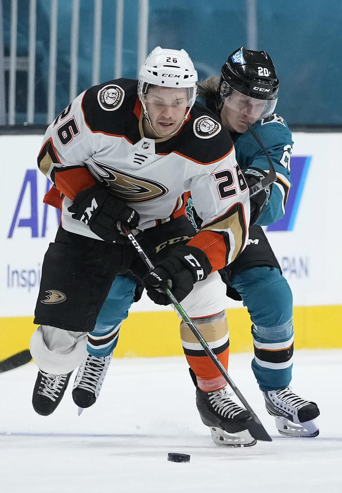 Anaheim Ducks left wing Andrew Agozzino (26) and San Jose Sharks left wing Marcus Sorensen (20) vie for the puck during the second period of an NHL hockey game, Monday, April 12, 2021, in San Jose, Calif. (AP Photo/Tony Avelar)