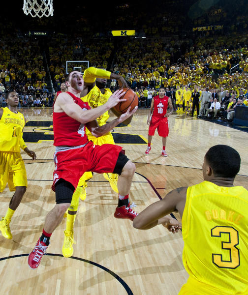 Ohio State guard Aaron Craft (4) has a layup attempt blocked by Michigan guard Tim Hardaway Jr., center back, in the final seconds of an NCAA college basketball game, Tuesday, Feb. 5, 2013, at Crisler Center in Ann Arbor, Mich. Michigan won 76-74 in overtime. (AP Photo/Tony Ding)