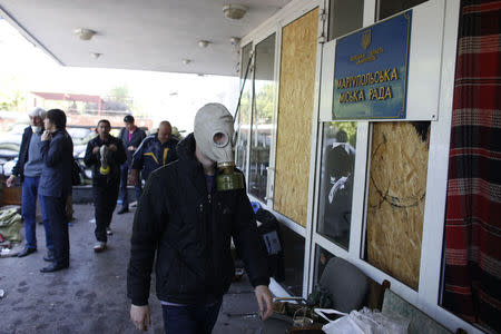 A pro-Russia rebel wearing a gas mask enters the city hall in Mariupol, eastern Ukraine May 7, 2014. REUTERS/Marko Djurica