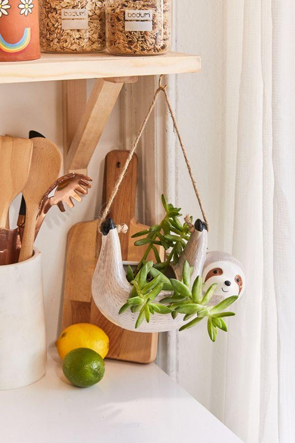 """<h2>Urban Outfitters Sloth Hanging Planter</h2> <br>One way to cheer up your WFH space? Re-pot your favorite green friend inside a happy hanging sloth planter.<br><br><strong>Urban Outfitters</strong> Sloth 4.25"""" Hanging Planter, $, available at <a href=""""https://www.urbanoutfitters.com/shop/sloth-425-hanging-planter"""" rel=""""nofollow noopener"""" target=""""_blank"""" data-ylk=""""slk:Urban Outfitters"""" class=""""link rapid-noclick-resp"""">Urban Outfitters</a><br>"""