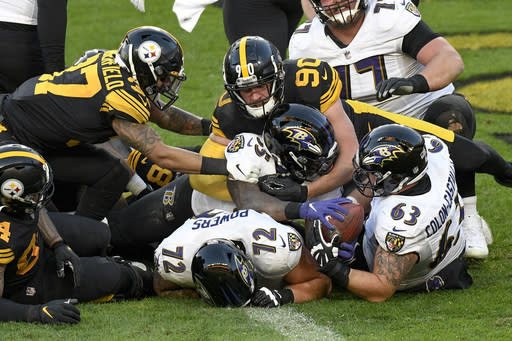 Baltimore Ravens running back Gus Edwards (35) gets into the end zone with a touchdown under Pittsburgh Steelers outside linebacker T.J. Watt (90) during the first half of an NFL football game, Wednesday, Dec. 2, 2020, in Pittsburgh. (AP Photo/Don Wright)