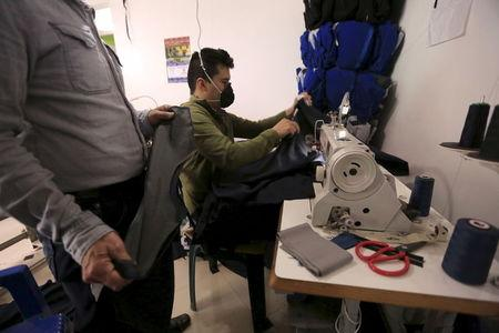 A former rebel who now owns a clothing factory oversees a worker in his workshop in Bogota