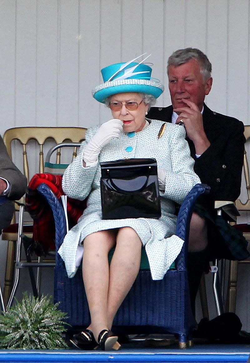 The Queen applies lipstick at the Braemar Gathering in Braemar. [Photo: PA]